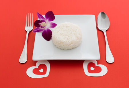 cooked rice with a spoon and fork on white dish and orchid on red background photo