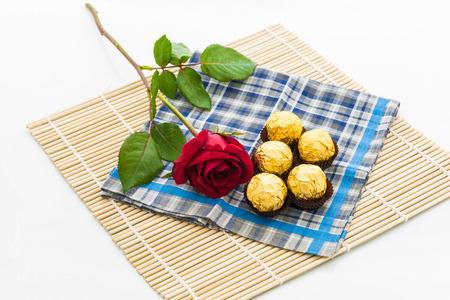 demure: red rose with handkerchief  and chocolate Ball, placemat on white background