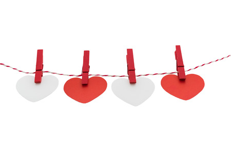 Love Valentines hearts and card natural cord and red clips hanging on white background, copy space photo