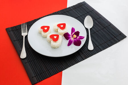 cooked rice heart shapes with a spoon and fork on white dish  in Platemat and on half of red and white background photo