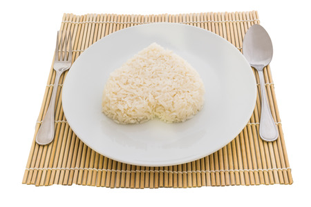 cooked rice heart shapes with a spoon and fork on white dish  in Platemat and on white background photo