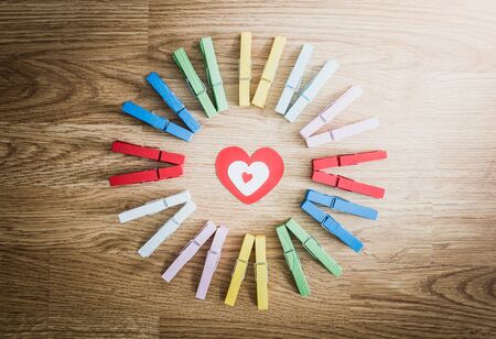 colorful wooden clothespin on wooden  background. arranged in a circle. love ideas and concepts photo