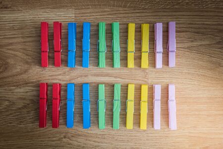 regularity: colorful wooden clothespin on wooden  background. arranged in a second row. Regularity ideas and concepts Stock Photo