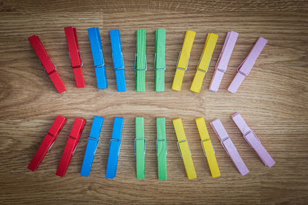 colorful wooden clothespin on wooden  background. arranged in a second row. Regularity ideas and concepts Stock Photo