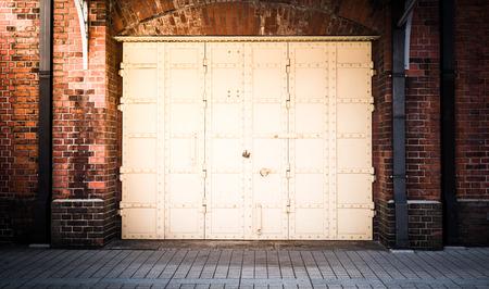 fachada: Puerta de acero en un fondo de pared de ladrillo rojo