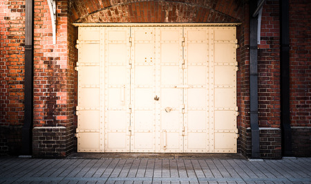 old brick wall: steel Door in a red brick wall background Stock Photo