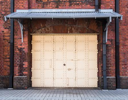 steel Door in a red brick wall background Imagens