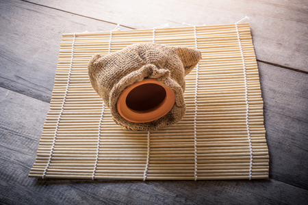 placemats: clay pot in sack bag on bamboo placemats and wooden background