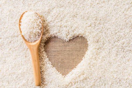 rice in wooden Spoon on rice background Space in the middle of a heart. sackcloth is background Imagens