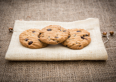 gunny: Stacked chocolate chip cookies on brown napkin over gunny  background in country style.