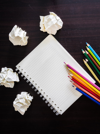 colored pencils: colored pencils and notebook on wood texture. Background for painting, drawing and sketching. Stock Photo