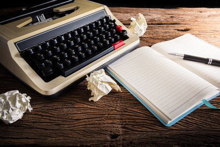 Vintage typewriter and a blank notebook , pen and crumpled paper, retro colors photo