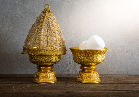 thailand culture: still life of Group of Thailand Gold tray with pedestal with The cover is made of lace on wooden table with grunge background. Thailand Culture Wedding Ceremony