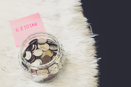money jar: many coins in a money jar with wedding label on jar. wedding concept. saving concept