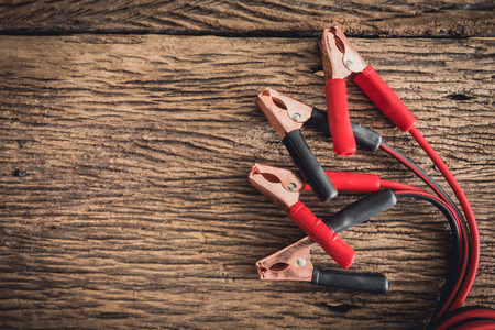 closeup of jumper cable for car battery on wooden background Archivio Fotografico