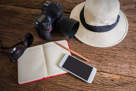 groups of objects: travel, summer vacation, tourism and objects concept. close up of hat, notebook, pencil, camera, smartphone and sunglasses on wooden table. Photo retro style