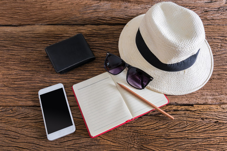 travel, summer vacation, tourism and objects concept. close up of hat, notebook, pencil, wallet, smartphone and sunglasses on wooden table. Photo retro style