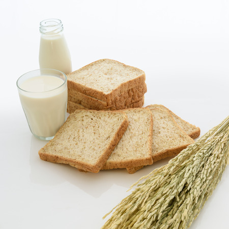 whole wheat bread: glass of milk and whole wheat bread on white background