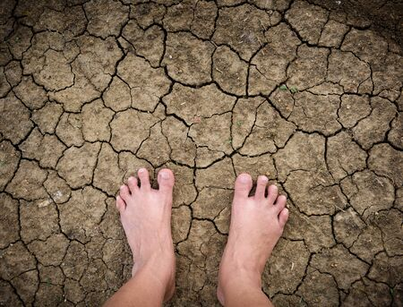 Barefoot standing on dry and cracked ground background and texture