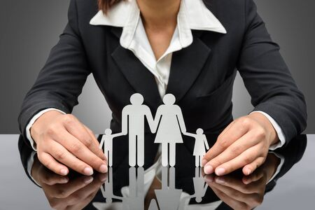 people, charity and care concept - close up of business woman hands holding paper family. isolated on white background with clipping path Stok Fotoğraf - 44168345