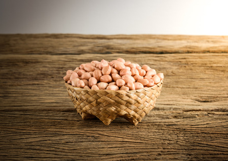 earthnuts: raw peanuts in basket Weave Wood on wooden table