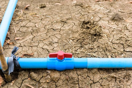 stop gate valve: Plastic Pipe Water valve on ground. ues for drip irrigation system. Stock Photo