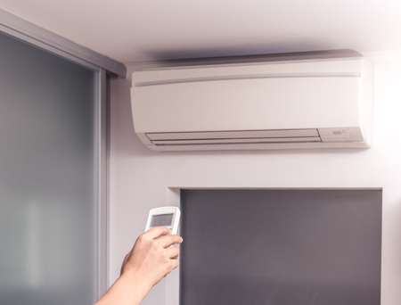 room air: Hand With Remote Control Directed On The Air Conditioner in the room