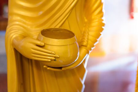 limosna: select focus of Buddha statue hand and alms bowl