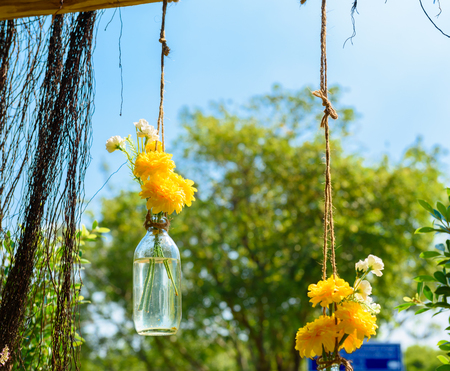 ramo de flores: Las flores de cal�ndula en una botella de cristal que cuelga. arreglos jarr�n de flores Foto de archivo