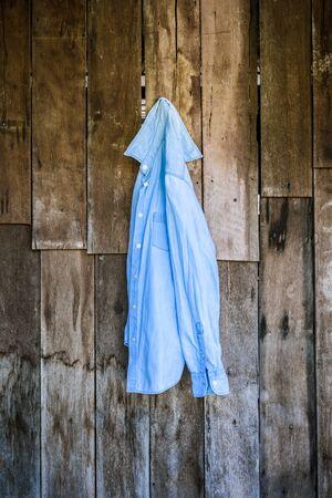 ropa colgada: pantalones vaqueros camiseta de las mujeres que cuelgan en la pared de fondo de madera