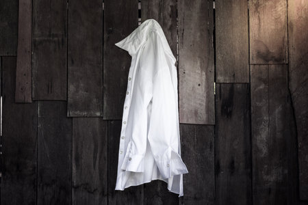 white shirt of women hanging on wooden wall background