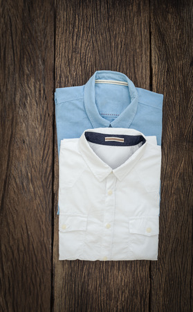 drycleaning: white Shirt and Jeans shirt  on wooden background Stock Photo