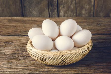 white eggs: still life basket of duck egg on grunge wooden background