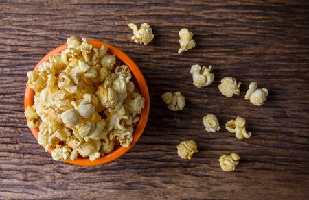 bowls of popcorn: Orange bowl of popcorn on a wooden table. top view