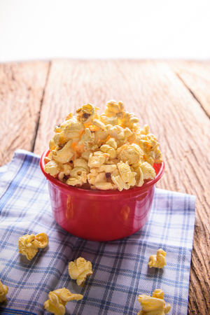 popcorn bowl: Homemade Sweet caramel popcorn in a bowl on blue cotton napkin against wooden background