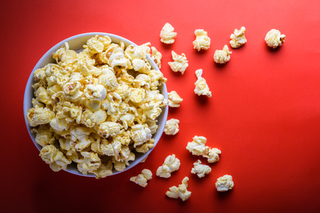 popcorn in white bowl on the red background, selective focus at popcorn in white bowl Stok Fotoğraf - 57995880