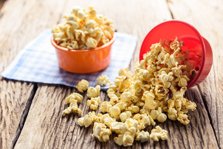 bowls of popcorn: Homemade Sweet caramel popcorn in a bowl on blue cotton napkin against wooden background