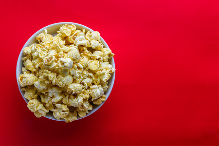 bowls of popcorn: popcorn in white bowl on the red background, selective focus at popcorn in white bowl