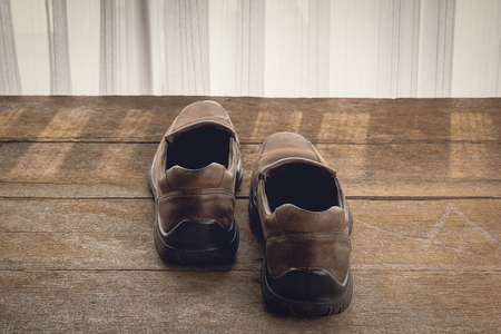 footgear: mens shoes Light and shadow from a window curtain on wooden background. Color retro style