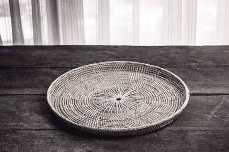 placemat: Wicker placemat on wooden background. Black and White Color Tone