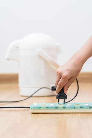 energized: Woman unplugged plug to save on energy. Power saving concept