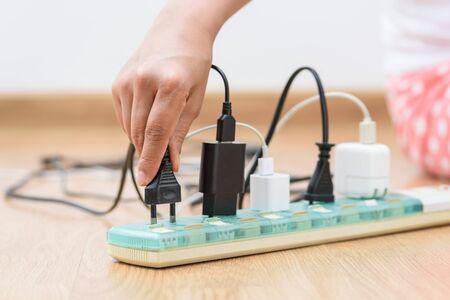Woman unplugged plug to save on energy. Power saving concept