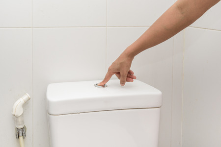 empty the bowel: womans finger pushing button and flushing toilet