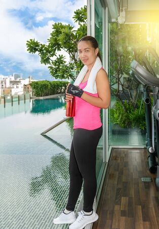 Gym woman working out drinking water at fitness center. Asian female fitness model inside in fitness center.