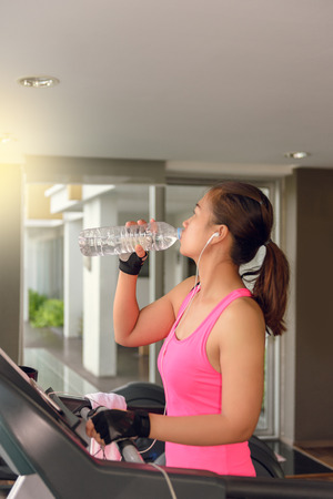 moon walker: Gym woman working out drinking water by moonwalker fitness machines. Asian female fitness model inside in fitness center. Stock Photo