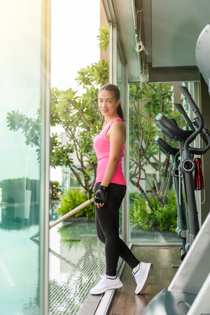 Tired woman after fitness time and exercising in gym at beautiful summer morning. Sport fitness model asian ethnicity training