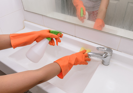 chores: woman doing chores in bathroom at home, cleaning sink and faucet with spray detergent