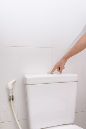 womans finger pushing button and flushing toilet