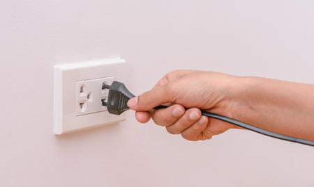 plugging: Female hand trying to plugging in appliance to electrical outlet in wall. Power saving concept