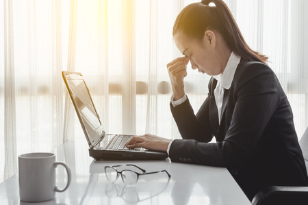 tensed: Businesswoman using computer in the office. Stress in the office